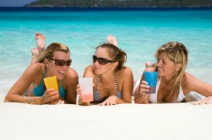 three women relaxing on tropical beach enjoying cocktails