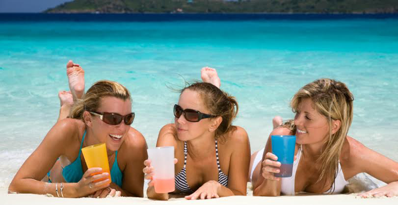 three women relaxing on tropical beach enjoying cocktails